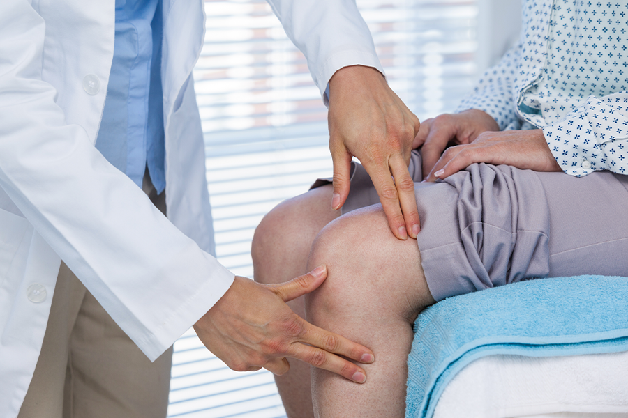 Doctor examines knee to determine if it causes shoulder pain in patient